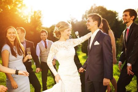 wesele: Pełna długość portret newlywed para tańca i zabawy z druhen i groomsmen w zielonym parku sunny