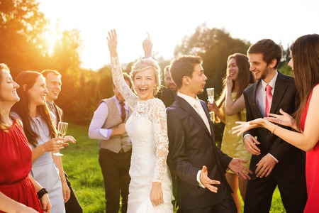 dancing woman: Full length portrait of newlywed couple dancing and having fun with bridesmaids and groomsmen in green sunny park