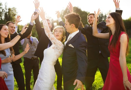 outdoor wedding: Full length portrait of newlywed couple dancing and having fun with bridesmaids and groomsmen in green sunny park