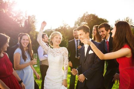 新婚者のカップル ダンスと緑豊かな日当たりの良い公園の新婦付け添人と花婿付け添人で楽しんでの完全な長さの肖像画