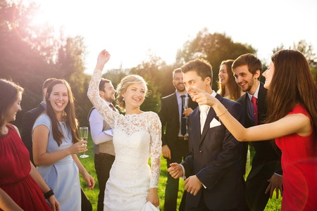 couple having fun: Full length portrait of newlywed couple dancing and having fun with bridesmaids and groomsmen in green sunny park