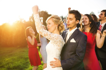 formal party: Full length portrait of newlywed couple dancing and having fun with bridesmaids and groomsmen in green sunny park