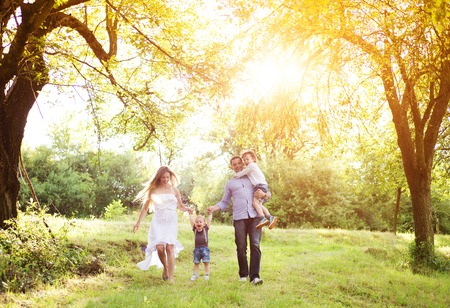 Happy young family spending time together outside in green nature. Archivio Fotografico