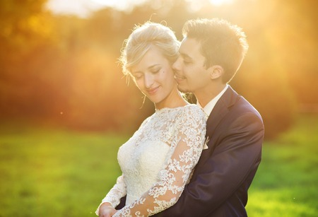 Young wedding couple enjoying romantic moments outside in summer park 版權商用圖片