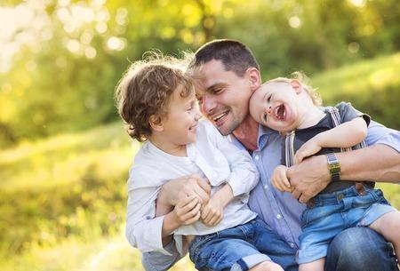 abrazar familia: Los ni�os peque�os y su padre que disfrutan de su tiempo juntos fuera en la naturaleza