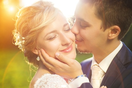 여름 초원에 밖에 서 로맨틱 한 순간을 즐기는 젊은 웨딩 커플