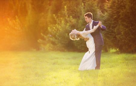 夏の公園の外ロマンチックな瞬間を楽しんでいる若い結婚式のカップル