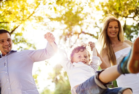 Happy young family spending time together outside in green nature. Standard-Bild