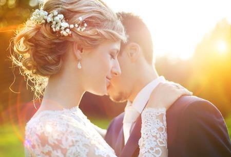 casamento: Pares novos do casamento curtindo momentos românticos fora em um prado do verão