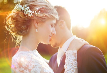 white flowers: Young wedding couple enjoying romantic moments outside on a summer meadow