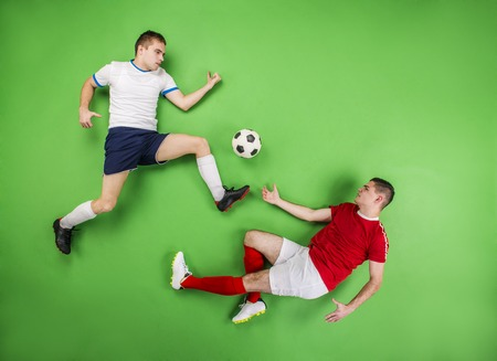 Two football players fighting for a ball. Studio shot on a green backgroud. photo