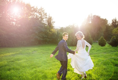 Young wedding couple enjoying romantic moments outside in summer park photo