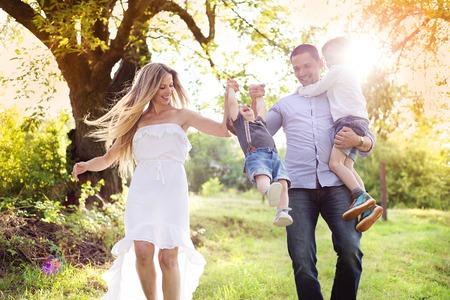 Feliz familia joven pasar tiempo juntos fuera en la naturaleza verde tiempo. Foto de archivo - 35406910