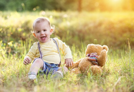 teddybear: Little boy playing and having fun outside in a park
