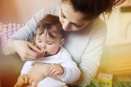 comiendo cereal: Joven madre y su peque�a hija desayunando juntos Foto de archivo