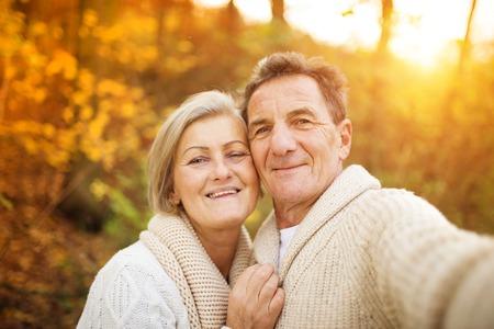 parejas caminando: Mayores activos que toman selfies de ellos fuera de la diversión en el bosque de otoño Foto de archivo