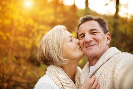 Actieve senioren nemen selfies van hen plezier buiten in de herfst bos Stockfoto