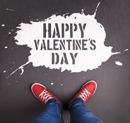 Original Valentines Day love concept with red sneakers and chalk drawn Happy Valentines Day title. photo