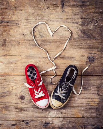 赤と黒のスニーカーで元バレンタインの愛の概念。スタジオ撮影、木製の床の背景。