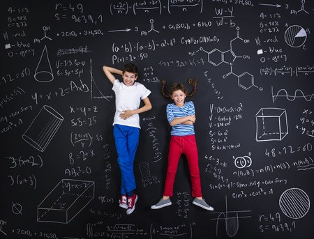school girl: Cute boy and girl learning playfully in frot of a big blackboard