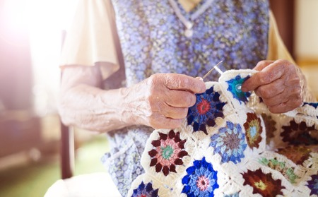 knitting: Old woman is knitting a blanket inside in her living room Stock Photo