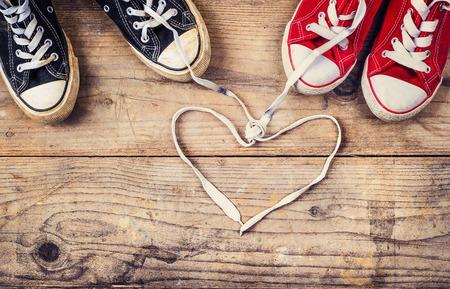 Originale concetto di amore di San Valentino con scarpe da ginnastica rosse e nere. Studio girato su un pavimento di legno sfondo. Archivio Fotografico - 35548125