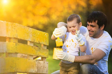 fence: Cute little boy and his father painting wooden fence together on sunny day in nature
