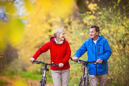 couple: Active seniors having walk with bike in autumn nature. They having romantic time outdoor.
