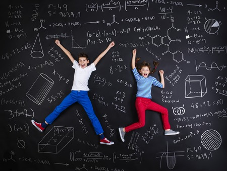 kids class: Cute boy and girl learning playfully in frot of a big blackboard