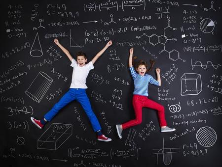 Leuke jongen en meisje leren op speelse wijze in frot van een groot schoolbord