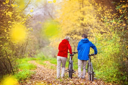 happy couple: Active seniors having walk with bike in autumn nature. They having romantic time outdoor.