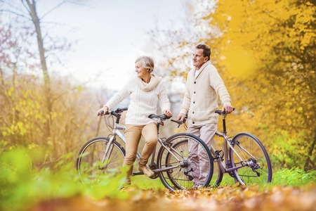 Active seniors riding bikes in autumn nature. They having romantic time outdoor. photo
