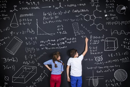 writing board: Cute boy and girl learning playfully in frot of a big blackboard