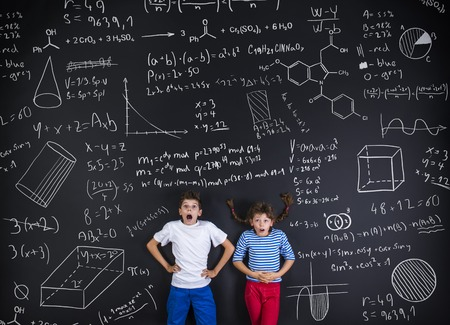 children writing: Cute boy and girl learning playfully in frot of a big blackboard