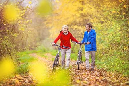 Actieve senioren hebben lopen met de fiets in de herfst de natuur. Ze dat romantische tijd buiten.