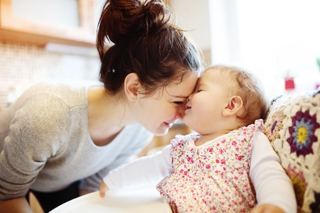 having breakfast: Young mother and her little daughter having breakfast together Stock Photo