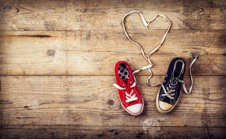 cuore: Originale concetto di amore di San Valentino con scarpe da ginnastica rosse e nere. Studio girato su un pavimento di legno sfondo.