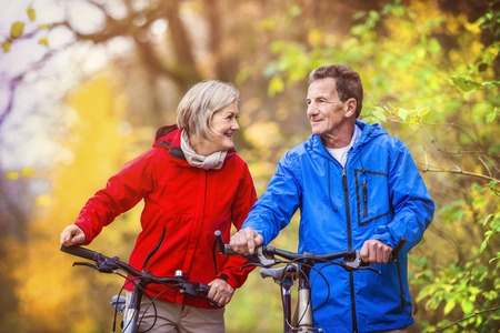 active woman: Active seniors having walk with bike in autumn nature. They having romantic time outdoor.