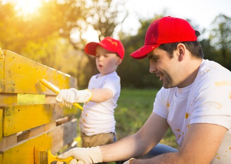 Cute little boy and his father in red caps painting wooden fence together on sunny day in nature photo