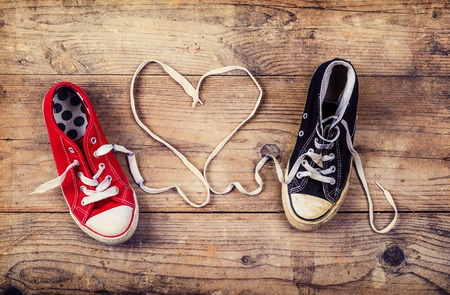 Original Valentine\'s Day love concept with red and black sneakers. Studio shot on a wooden floor background. Banque d'images