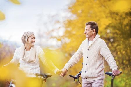 秋の自然の中バイクに乗ってアクティブ シニア。彼らは屋外のロマンチックな時間を持っています。