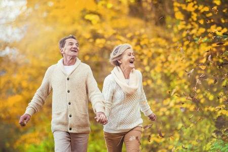 Active seniors having fun and playing with the leaves in autumn forest photo