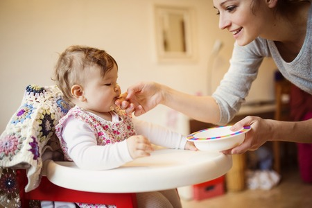 mealtime: Young mother and her little daughter having breakfast together Stock Photo