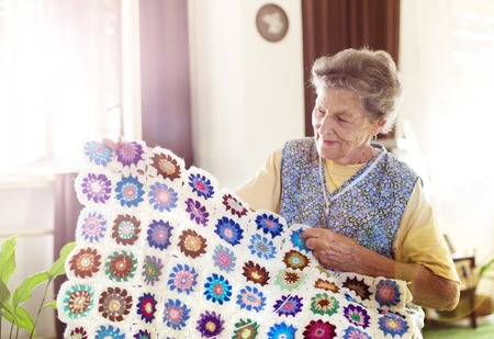 Old woman is knitting a blanket inside in her living room Stock Photo