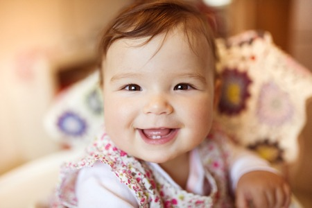 baby tooth: Cute little baby sitting in a high chair happy after being fed by her mother