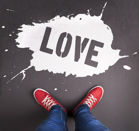 Original Valentines Day love concept with red sneakers and chalk drawn love title. photo