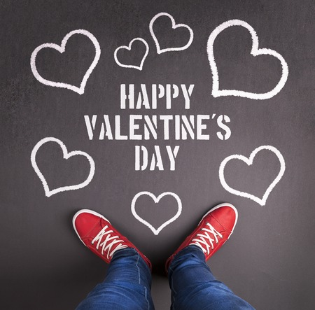 Original Valentines Day love concept with red sneakers and chalk drawn heart symbol. photo