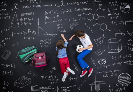 schoolbag: Cute boy and girl learning playfully in frot of a big blackboard