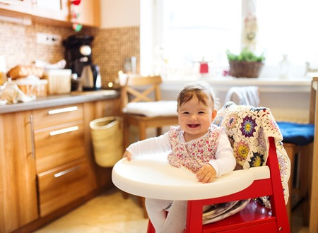 baby with spoon: Young mother and her little daughter having breakfast together Stock Photo