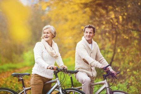 tercera edad: Mayores activos andar en bicicleta en la naturaleza de oto�o. Ellos tienen rom�ntico tiempo al aire libre.